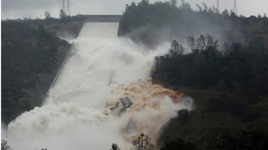 Water flows through break in the wall of the Oroville Dam spillway, Thursday.