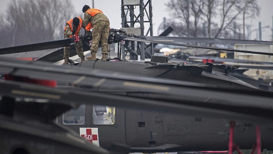 U.S. Technicians prepare a helicopter for the transport in Bremerhaven, northern Germany, Sunday Feb. 12, 2017. The U.S. Army has begun unloading dozens of Chinook, Apache and Black Hawk helicopters at the northern German port of Bremerhaven, to be moved to the Bavarian town of Illesheim, Germany.  Some of them will be taken on stints to Lithuania and Romania. (Ingo Wagner/dpa via AP)