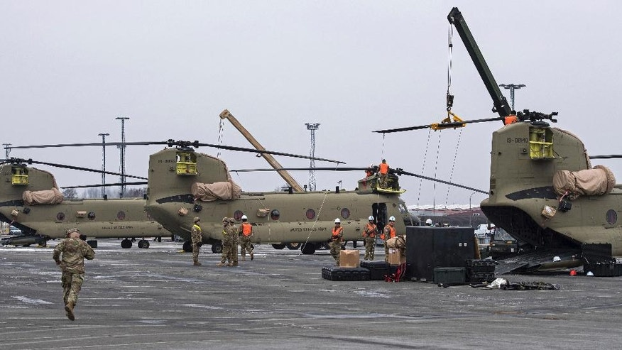 U.S. Technicians prepare  helicopters for the transport in Bremerhaven, northern Germany, Sunday Feb. 12, 2017. The U.S. Army has begun unloading dozens of Chinook, Apache and Black Hawk helicopters at the northern German port of Bremerhaven, to be moved to the Bavarian town of Illesheim, Germany.  Some of them will be taken on stints to Lithuania and Romania. (Ingo Wagner/dpa via AP)