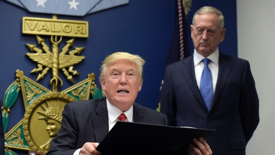 FILE - In this Jan. 27, 2017 file photo, President Donald Trump, left, with Defense Secretary James Mattis, right, watching, explains the executive action on extreme vetting that he is about to sign at the Pentagon in Washington. American forces were perched high on the top of the Bashiq Mountain, calling in airstrikes that pounded Islamic State militants. Down below, Kurdish forces rolled past to recapture in the ancient city of Sinjar.  (AP Photo/Susan Walsh)