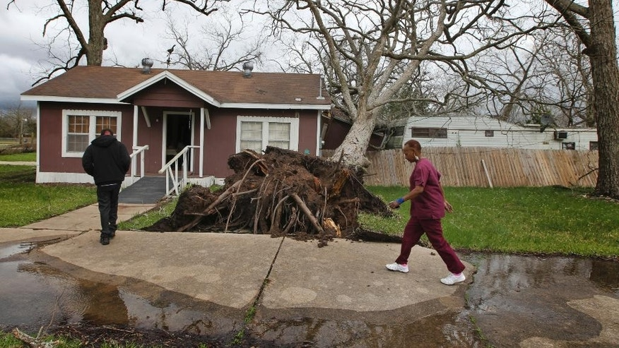 Cheryl Bradshaw, right, and her son Jerard walk past a toppled tree that separated her bathroom from her home Tuesday, Feb. 14, 2017 in Wharton, Texas.  Tornadoes are suspected of damaging homes and injuring people Tuesday southwest of Houston as a strong storm system moved quickly across much of the state. (Steve Gonzales/Houston Chronicle via AP)