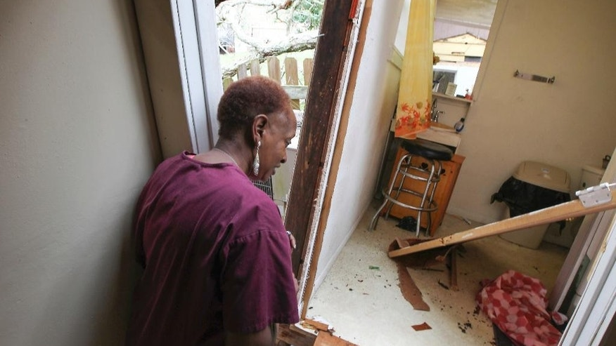 Cheryl Bradshaw looks at what is left of her only bathroom after a tree fell on her home Tuesday, Feb. 14, 2017 in Wharton, Texas. Tornadoes are suspected of damaging homes and injuring people Tuesday southwest of Houston as a strong storm system moved quickly across much of the state. (Steve Gonzales/Houston Chronicle via AP)
