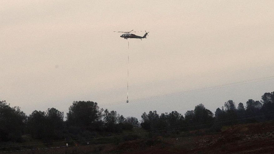 A helicopter lowers a bag of rocks to be dropped on a hole on the lip of the Oroville Dam's emergency spillway Monday, Feb. 13, 2017, in Oroville, Calif. The barrier, at the nation's tallest dam, is being repaired a day after authorities ordered mass evacuations for everyone living below the lake out of concerns the spillway could fail. (AP Photo/Rich Pedroncelli)