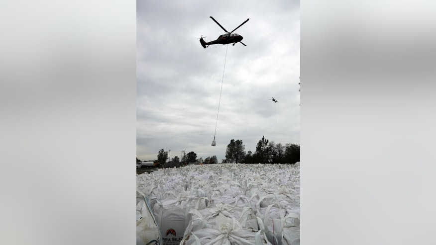 A helicopter carries sandbags in the direction of a damaged dam Wednesday, Feb. 15, 2017, in Oroville, Calif. The Oroville Reservoir is continuing to drain Wednesday as state water officials scrambled to reduce the lake's level ahead of impending storms. (AP Photo/Marcio Jose Sanchez)