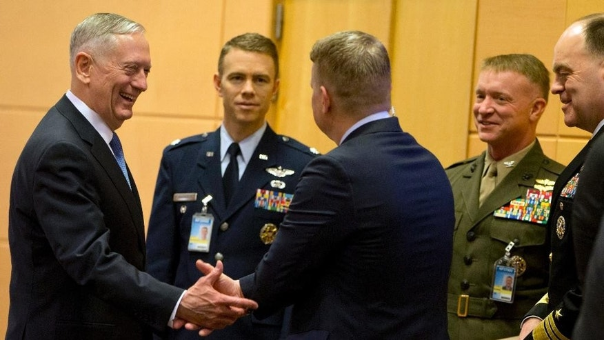 U.S. Secretary of Defense Jim Mattis, left, speaks with members of his delegation prior to a meeting at NATO headquarters in Brussels on Wednesday, Feb. 15, 2017. For U.S. Defense Secretary Jim Mattis, the next few days will be a reassurance tour with a twist. He is expected to tell allies the U.S. is committed to NATO and is also hoping to secure bigger defense spending commitments. (AP Photo/Virginia Mayo, Pool)