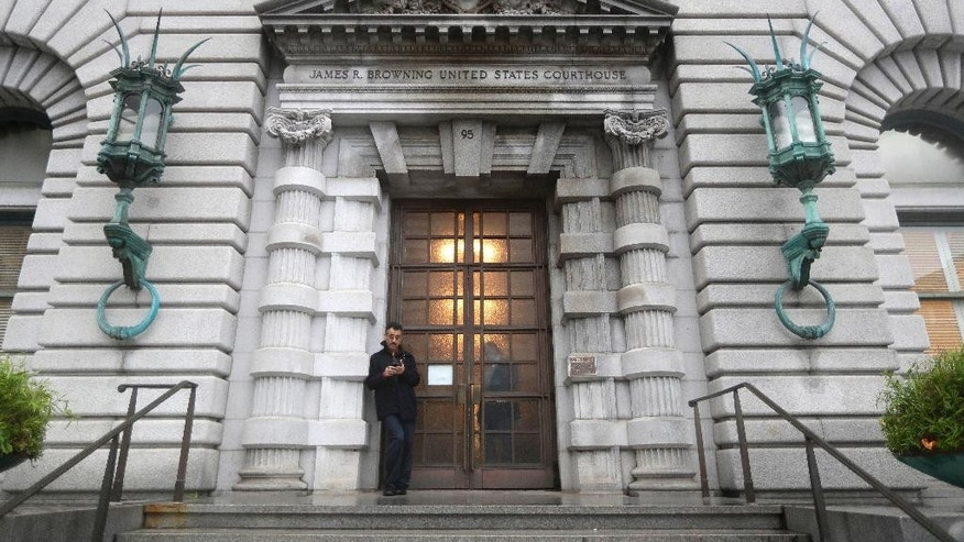 FILE - In this Feb.9, 2017 file photo, a man stands outside the main door outside the 9th U.S. Circuit Court of Appeals building in San Francisco. The state of Texas on Wednesday, Feb. 15, 2017, defended President Donald Trump's ban on travelers from seven predominantly Muslim nations as an assertion of presidential authority intended to protect the country from terrorists, splitting with states that have denounced the order as a religious attack. (AP Photo/Marcio Jose Sanchez, file)