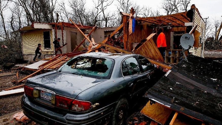 Eurelio Lopez, 8, left, runs into what is left of his home after storm Tuesday, Feb. 14, 2017, in Van Vleck, Texas. Tornadoes are suspected of damaging homes and knocking out power southwest of Houston as part of a strong storm system that moved quickly across much of the state. (Michael Ciaglo/Houston Chronicle via AP)