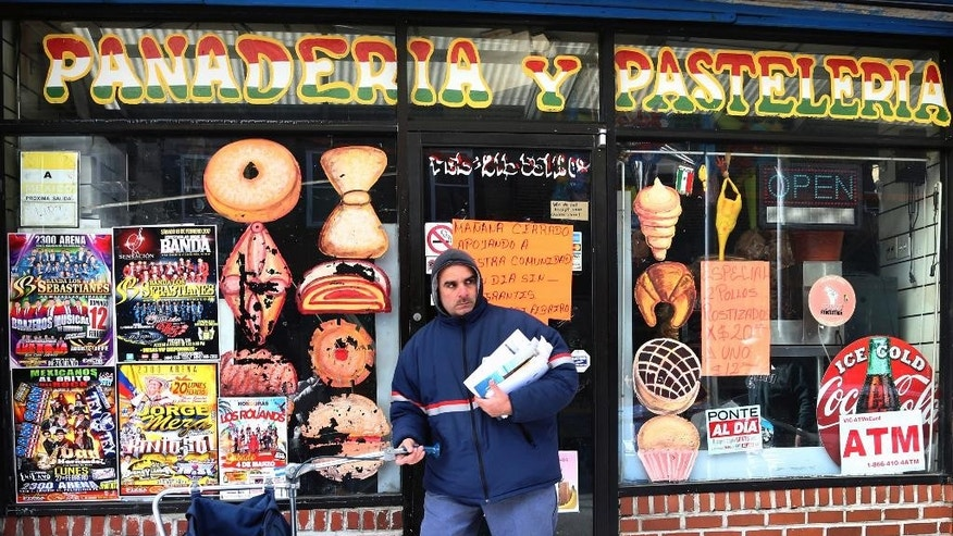 "A mail carrier passes a closed bakery Thursday, Feb. 16, 2017, in south Philadelphia's Italian Market. In an action called ""A Day Without Immigrants"", immigrants across the country are expected to stay home from school and work on Thursday to show how critical they are to the U.S. economy and way of life. (AP Photo/Jacqueline Larma)"