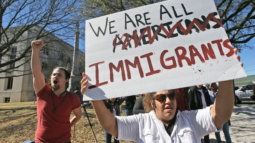"Protesters chant outside the Grayson County courthouse in downtown Sherman, Texas, Thursday, Feb. 16, 2017. In an action called ""A Day Without Immigrants,"" immigrants across the country are expected to stay home from school, work and close businesses to show how critical they are to the U.S. economy and way of life. (AP Photo/LM Otero)"