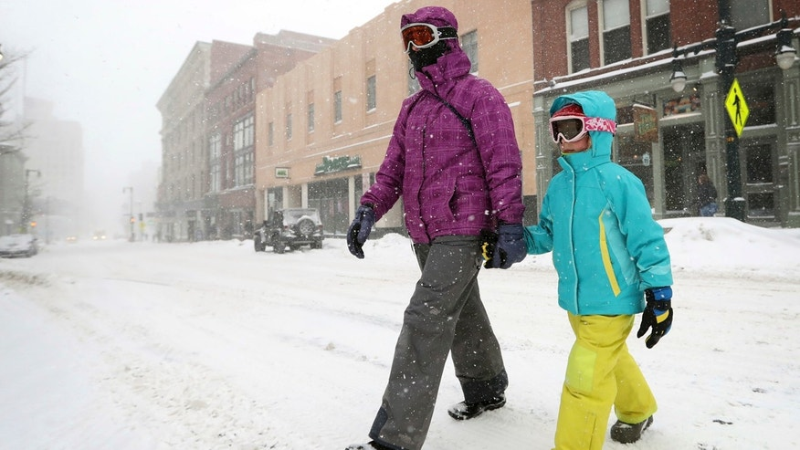 Christine Stack and her daughter, Carina Stack, 6, wear goggles while walking during a snowstorm, Thursday, Feb 9, 2017, in Portland, Maine.