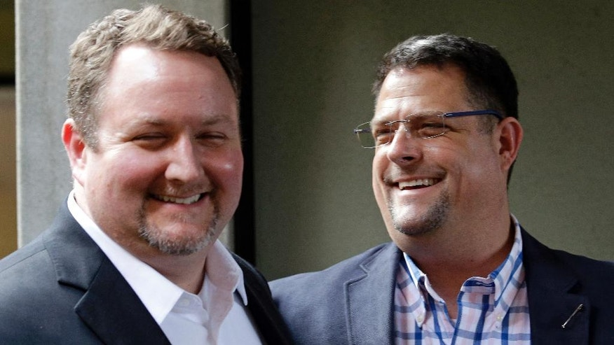 FILE - In this Nov. 15, 2016, file photo, Curt Freed, left, and his husband Robert Ingersoll, the couple who sued florist Barronelle Stutzman for refusing to provide services for their wedding, smile after a hearing before Washington's Supreme Court in Bellevue, Wash.