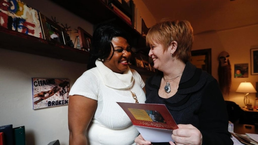 Lucy Neighbor laughs with Deborah Drennan, Freedom House's executive director, Friday, Feb. 10, 2017, in Detroit. With the help of several people, Neighbor escaped a jail where she was beaten and raped, secured a passport and U.S. tourist visa, and eventually found her way to Freedom House's front door in January 2008 from Cameroon. Neighbor, whose husband was fatally beaten during a government protest in their homeland, wasn't sure exactly what it was but felt at home the moment a worker from Africa opened the door.(AP Photo/Paul Sancya)