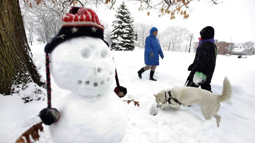 Tina Fuller, 60, of Waltham, Mass., behind center, walks past a snowman and a person walking a dog, Sunday, Feb. 12, 2017, in Waltham, Mass.