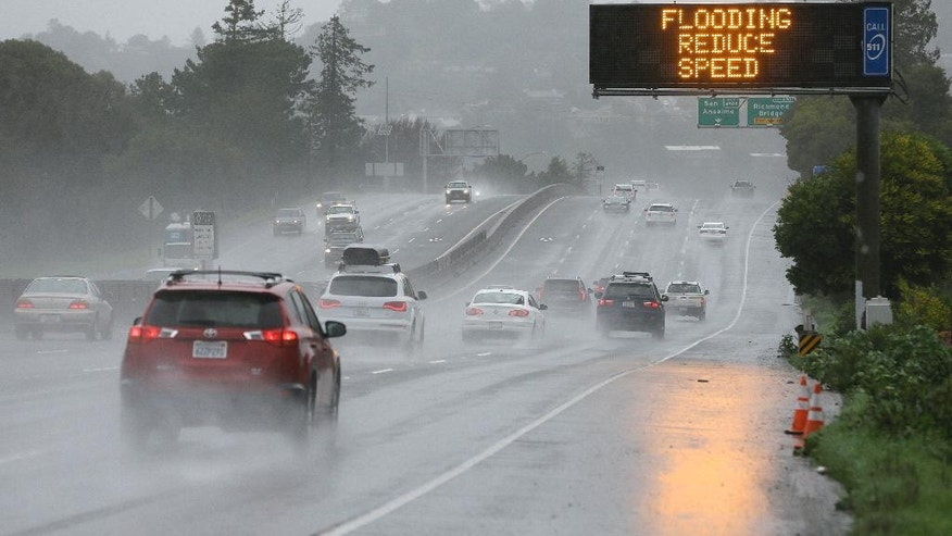 A sign warns motorists of flooding on northbound Highway 101, Monday, Feb. 20, 2017, in Corte Madera, Calif. Heavy downpours are swelling creeks and rivers and bringing threats of flooding in California's already soggy northern and central regions. The National Weather Service map shows floods, snow and wind advisories for the northern part of the state.(AP Photo/Eric Risberg)