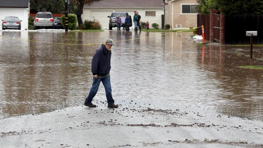 A man walks on a flooded street Monday, Feb. 20, 2017, in Salinas, Calif. Forecasters issued flash flood warnings Monday throughout the San Francisco Bay Area and elsewhere in Northern California as downpours swelled creeks and rivers in the already soggy region. (Nic Coury/Monterey County Weekly via AP)