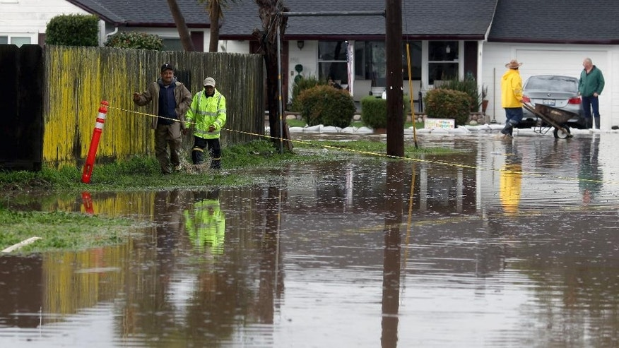 Residents walk down a flooded road on Monday, Feb. 20, 2017, in Salinas, Calif. Forecasters issued flash flood warnings Monday throughout the San Francisco Bay Area and elsewhere in Northern California as downpours swelled creeks and rivers in the already soggy region. (Nic Coury/Monterey County Weekly via AP)