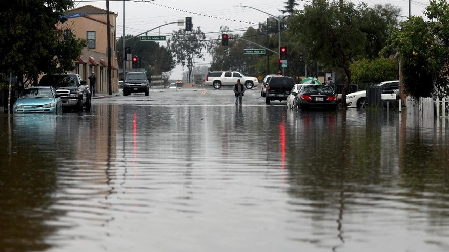 A man walks through floodwaters Monday, Feb. 20, 2017, in Salinas, Calif. Forecasters issued flash flood warnings Monday throughout the San Francisco Bay Area and elsewhere in Northern California as downpours swelled creeks and rivers in the already soggy region. (Nic Coury/Monterey County Weekly via AP)