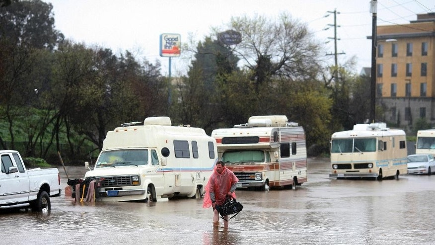 A man who lives in his RV, which was parked in the 300 block of Griffith Street in Salinas, Calif., walks through the flooded street on Mon., Feb. 20, 2016. ~ OUT: MONTEREY HERALD, SALINAS CALIFORNIAN, SANTA CRUZ SENTINEL, MONTEREY COUNTY TELEVISION NEWSMonday, Feb. 20, 2017, in Salinas, Calif. Forecasters issued flash flood warnings Monday throughout the San Francisco Bay Area and elsewhere in Northern California as downpours swelled creeks and rivers in the already soggy region. (Nic Coury/Monterey County Weekly via AP)
