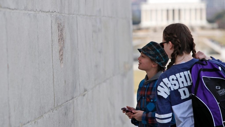 With the Lincoln Memorial in the background, people look at graffiti on the Washington Monument, Tuesday, Feb. 21, 2017, in Washington. U.S. Park Police spokeswoman Sgt. Anna Rose said that the messages written in permanent marker were discovered over the holiday weekend at the Lincoln Memorial, the Washington Monument and the World War II Memorial. (AP Photo/Alex Brandon)