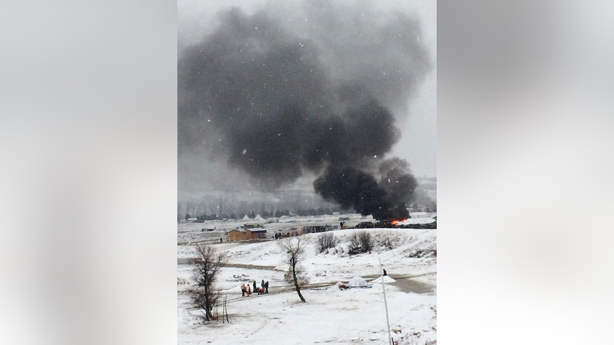 Dakota Access pipeline opponents burn structures in their main protest camp in southern North Dakota near Cannon Ball on Wednesday, Feb. 22, 2017, as authorities prepare to shut down the camp in advance of spring flooding season. (AP Photo/Blake Nicholson)