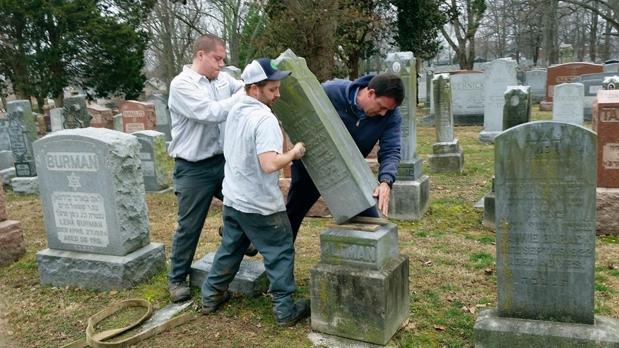 Rosenbloom Monument Co. workers from left, Nathan Fohne, Derek Doolin and Philip Weiss hoist a headstone at the Chesed Shel Emeth Cemetery in University City, Mo., where over 150 headstones were tipped over.