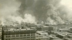 In this undated photo provided by Tulsa Historical Society and Museum, Greenwood neighborhood also known as Black Wall Street in Tulsa, Okla., is burned down during a race riot in 1921. The once-prosperous section of Tulsa that became the site of one of the worst race riots in American history is attempting to remake itself again after decades of neglect. Black leaders want to bring 100 new companies to the former Black Wall Street in north Tulsa by 2021, the 100th anniversary of its fall. (Courtesy of Tulsa Historical Society & Museum via AP)