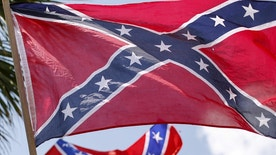 A member of the Ku Klux Klan yells as he flies a Confederate flag during a rally at the statehouse in Columbia, South Carolina July 18, 2015. A Ku Klux Klan chapter and an African-American group planned overlapping demonstrations on Saturday outside the South Carolina State House, where state officials removed the Confederate battle flag last week. REUTERS/Chris Keane? - RTX1KUT1