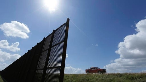 "FILE - In this Sept. 6, 2012, file photo, cotton farmer Teofilo ""Junior"" Flores drives his truck along the U.S.-Mexico border fence that passes through his property in Brownsville, Texas. President Donald Trump's vow to accelerate construction of a ""contiguous, physical wall"" along the Mexican border is slamming into a Washington reality _ who's going to pay for it and how? (AP Photo/Eric Gay, File)"