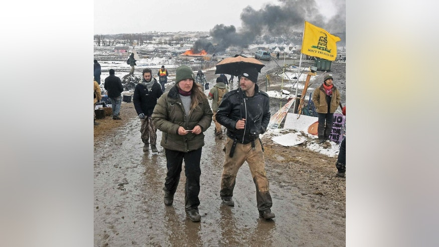 Tribune Tori Ramos, left, and Riley Cogburn, both of Albany, N.Y., leave as opponents of the Dakota Access pipeline leave their main protest camp Wednesday, Feb. 22, 2017, near Cannon Ball, N.D. Most of the pipeline opponents abandoned their protest camp Wednesday ahead of a government deadline to get off the federal land, and authorities moved to arrest some who defied the order in a final show of dissent. (Tom Stromme/The Bismarck Tribune via AP)