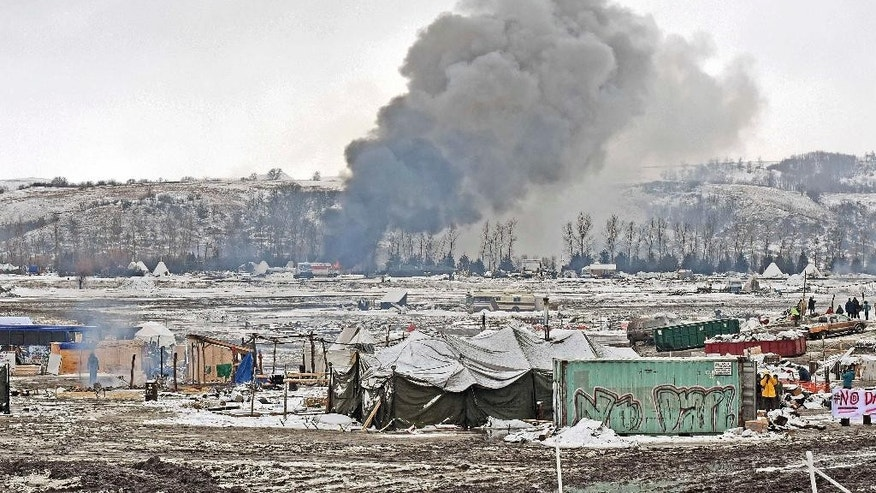 Smoke from fires set by protesters goes up as they leave their protest camp on U.S. Army Corps of Engineers property in southern Morton County, near Cannon Ball, N.D., Wednesday, Feb. 22, 2017. Most of the Dakota Access pipeline opponents abandoned their protest camp Wednesday ahead of a government deadline to get off the federal land, and authorities moved to arrest some who defied the order in a final show of dissent. Earlier in the day, some of the last remnants of the camp went up in flames when occupants set fire to makeshift wooden housing as part of a leaving ceremony. (Tom Stromme/The Bismarck Tribune via AP)
