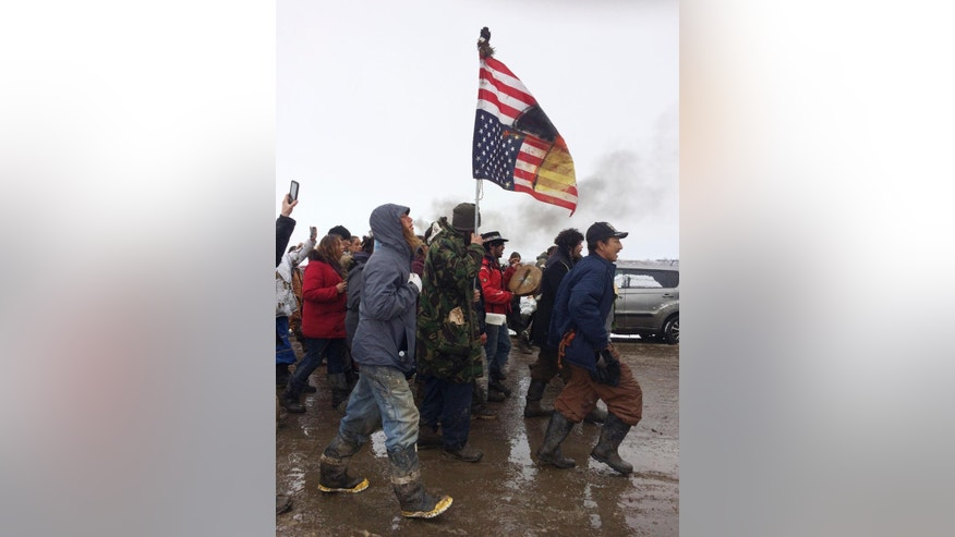 People peacefully leave the Dakota Access pipeline main protest camp near Cannon Ball, N.D., as authorities prepare to shut it down in advance of the spring flooding season. The Army Corps of Engineers ordered the camp closed at 2 p.m. Wednesday. (AP Photo/Blake Nicholson)
