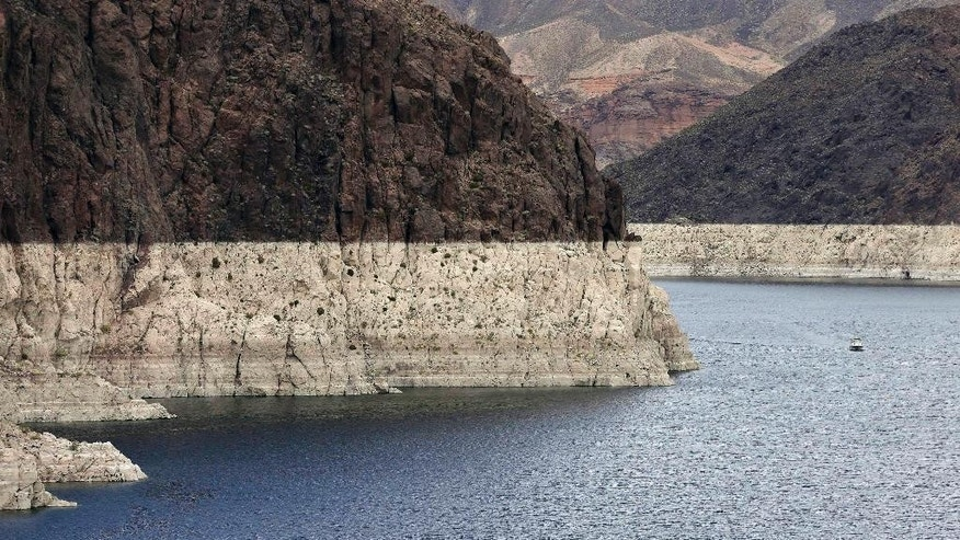 "FILE – In this April 16, 2013 file photo, a ""bathtub ring"" marks the high water mark as a recreational boat approaches Hoover Dam along Black Canyon on Lake Mead, the largest Colorado River reservoir, near Boulder City, Nev. Scientists say global warming may already be shrinking the Colorado River and could reduce its flow by more than a third by the end of the century. (AP Photo/Julie Jacobson, File)"