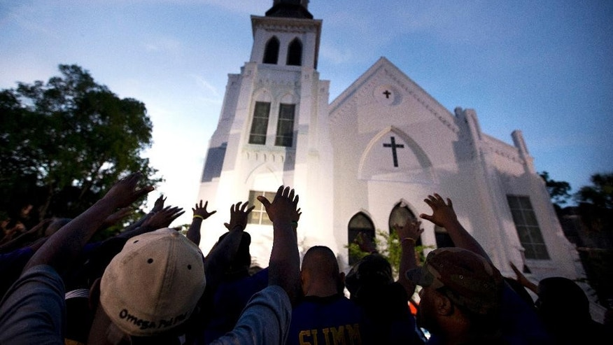 FILE -In this Friday, June 19, 2015 file photo, the men of Omega Psi Phi Fraternity Inc. lead a crowd of people in prayer outside the Emanuel AME Church, after a memorial for the nine people killed by Dylann Roof in Charleston, S.C. Nearly a month after returning a death sentence against Roof for the racist church massacre, the jurors in his case visited the house of worship on Feb. 5, 2017, for a Sunday service. (AP Photo/Stephen B. Morton, File)