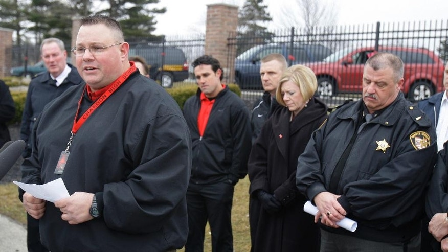 FILE – In this March 1, 2012, file photo, Chardon High School assistant football coach Frank Hall, second from left, speaks during a news conference in Chardon, Ohio. Hall, who chased shooter T.J. Lane from the high school and prayed with dying victims five years ago on Feb. 27, 2012, tells The Plain Dealer he still thinks about how he could've stopped the shooter and feels he let down the three boys who died and a fourth who was paralyzed. Lane is serving life in prison. (AP Photo/Tony Dejak, File)