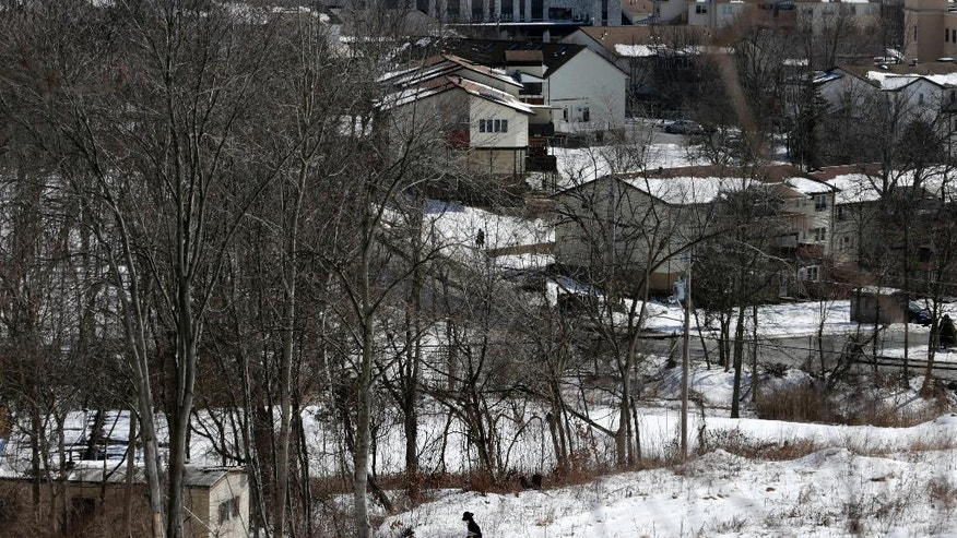 In this Feb. 16, 2017 photo, a Hasidic man walks through the snow in Kiryas Joel, N.Y. Kiryas Joel is an increasingly crowded Hasidic village northwest of New York City - an enclave of bearded men in black coats, women in head scarves and many, many babies surrounded by suburbia. (AP Photo/Seth Wenig)