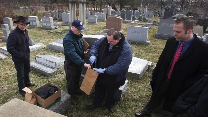 Jim McReynolds, center, from the Philadelphia Police northeast detectives unit, places items from the scene in a bag for further investigation Monday, Feb. 27, 2017, at Mount Carmel Cemetery in Philadelphia. More than 100 headstones have been vandalized at the Jewish cemetery in Philadelphia, damage discovered less than a week after similar vandalism in Missouri, authorities said. (AP Photo/Jacqueline Larma)