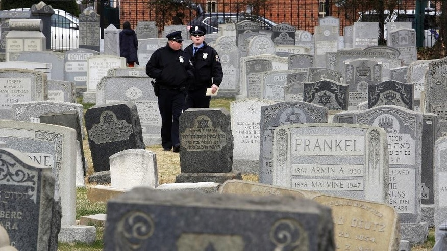 Philadelphia Police walk through Mount Carmel Cemetery, Monday, Feb. 27, 2017, in Philadelphia. More than 100 headstones have been vandalized at the Jewish cemetery in Philadelphia, damage discovered less than a week after similar vandalism in Missouri, authorities said. (AP Photo/Jacqueline Larma)
