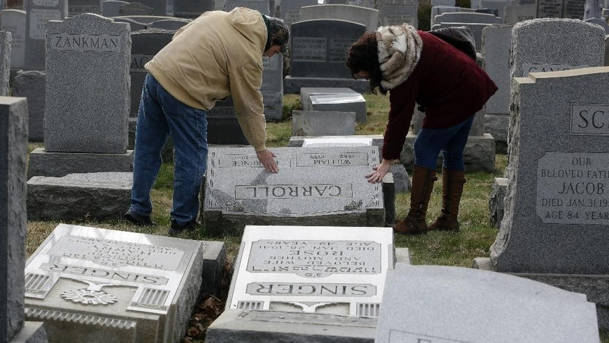 Joe Nicoletti and Ronni Newton of the Taconey Holmesburg town watch group pay their respects at a damaged headstone in Mount Carmel cemetery Monday, Feb. 27, 2017, in Philadelphia. More than 100 headstones have been vandalized at the Jewish cemetery in Philadelphia, damage discovered less than a week after similar vandalism in Missouri, authorities said.(AP Photo/Jacqueline Larma)