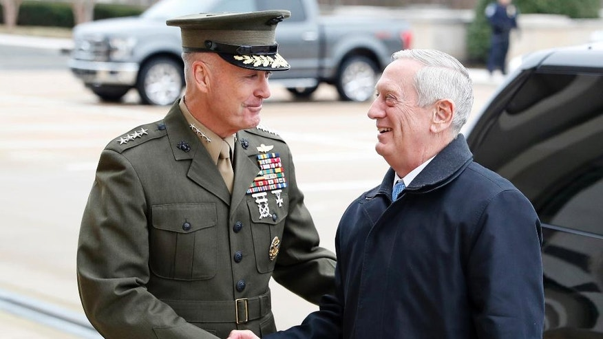 "FILE - In this Jan. 21, 2107 file photo, Joint Chiefs Chairman Gen. Joseph Dunford greets Defense Secretary Jimn Mattis at the Pentagon. A new military strategy to meet President Donald Trump's demand ""to obliterate"" the Islamic State group is likely to deepen U.S. military involvement in Syria, possibly with more ground troops, even as the current U.S. approach in Iraq appears to be working and will require fewer changes. Dunford said Feb. 23 that the strategy will take aim not just at the Islamic State but at al-Qaida and other extremist organizations in the Middle East and beyond whose goal is to attack the United States. He emphasized that it would not rest mainly on military might. (AP Photo/Alex Brandon, File)"