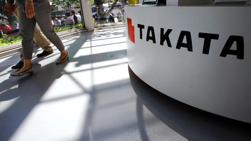 FILE - In this May 4, 2016, file photo, visitors walk by a Takata Corp. desk at an automaker's showroom in Tokyo. Japanese auto parts maker Takata Corp. is expected to plead guilty in U.S. District Court in Detroit on Monday, Feb. 27, 2017, to a criminal charge and agree to a $1 billion penalty for concealing a deadly air bag inflator problem. (AP Photo/Shizuo Kambayashi, File)