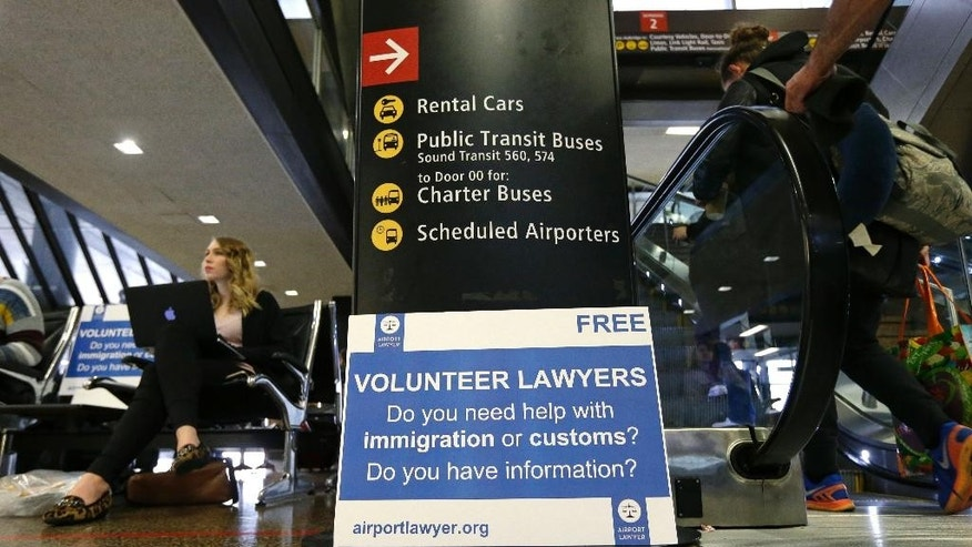 Asti Gallina, left, a volunteer law student from the University of Washington, sits at a station near where passengers arrive on international flights at Seattle-Tacoma International Airport Tuesday, Feb. 28, 2017, in Seattle. Gallina was volunteering with the group Airport Lawyer, which also offers a secure website and mobile phone app that alerts volunteer lawyers to ensure travelers make it through customs without trouble. Airport officials and civil rights lawyers around the country are getting ready for President Donald Trump's new travel ban, which is expected to be released as soon as Wednesday. (AP Photo/Ted S. Warren)