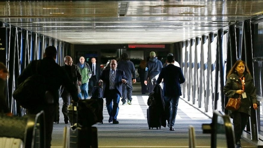 Pedestrians walk through a skybridge at Seattle-Tacoma International Airport near the international arrivals area, Tuesday, Feb. 28, 2017, in Seattle. Airport officials and civil rights lawyers around the country are getting ready for President Donald Trump's new travel ban, which is expected to be released as soon as Wednesday. (AP Photo/Ted S. Warren)