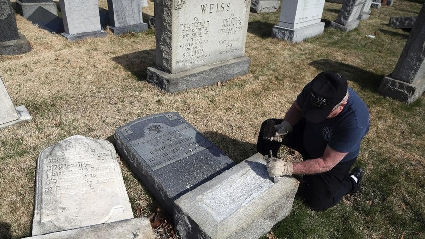 Trump supporter Bob, who declined to give his last name, volunteers his time and prepares the base of a damaged headstone Tuesday, Feb. 28, 2017, in Philadelphia. Scores of volunteers are expected to help in an organized effort to clean up and restore the Jewish cemetery where vandals damaged hundreds of headstones.(AP Photo/Jacqueline Larma)