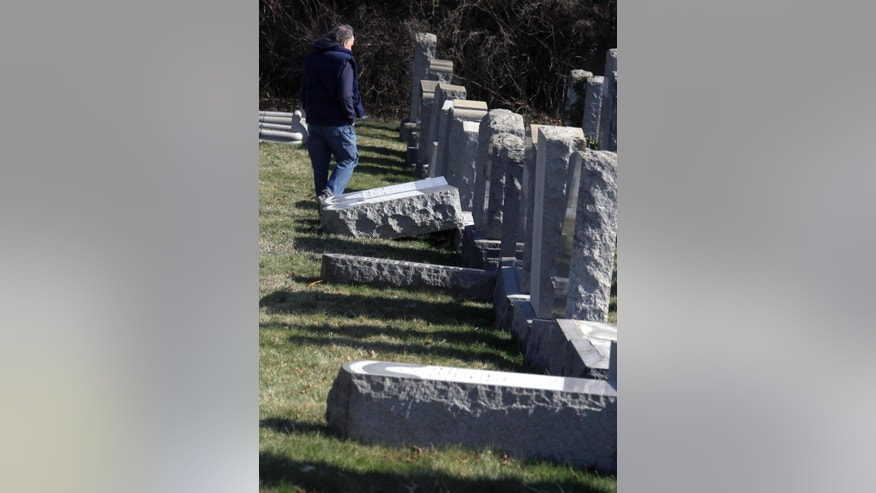 A visitor looks at damaged headstones at Mount Carmel Cemetery Tuesday, Feb. 28, 2017, in Philadelphia. Scores of volunteers are expected to help in an organized effort to clean up and restore the Jewish cemetery where vandals damaged hundreds of headstones. (AP Photo/Jacqueline Larma)