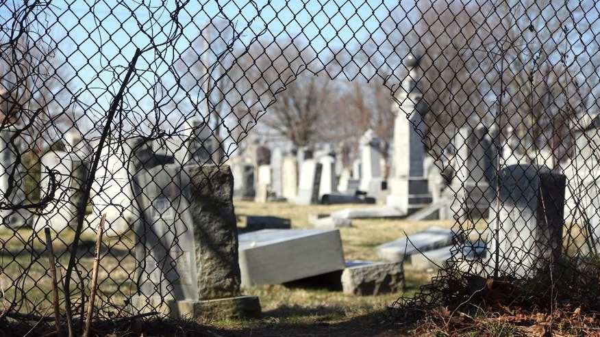 Damaged headstones are seen through a hole in a fence surrounding Mount Carmel Cemetery Tuesday, Feb. 28, 2017, in Philadelphia. Scores of volunteers are expected to help in an organized effort to clean up and restore the Jewish cemetery where vandals damaged hundreds of headstones. (AP Photo/Jacqueline Larma)