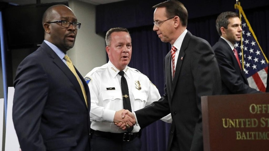 Baltimore Police Department Commissioner Kevin Davis, center, shakes hands with U.S. Attorney for the District of Maryland Rod J. Rosenstein after a news conference in Baltimore, Wednesday, March 1, 2017, to announce that seven Baltimore police officers who worked on a firearms crime task force are facing charges of stealing money, property and narcotics from people over two years. Standing at left is Assistant Special Agent in Charge Don A. Hibbert of the DEA's Baltimore District Office. (AP Photo/Patrick Semansky)