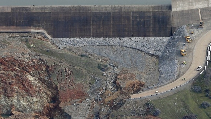 Feb. 13, 2017: This photo shows erosion caused when overflow water cascaded down the emergency spillway, right, of the Oroville Dam in Oroville, Calif.