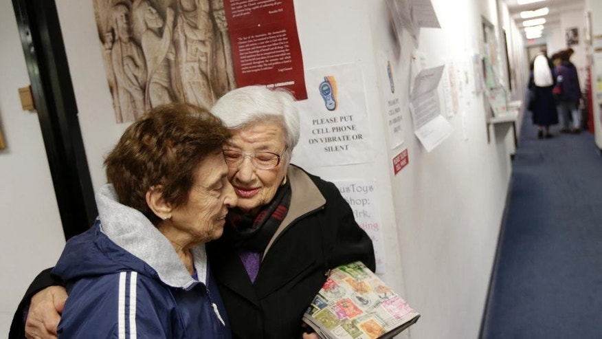Lorice Hanna, left, and Elvira Lacitignola hug after one of the last masses at the Chapel on the Mall on Ash Wednesday, March 1, 2017, in Paramus, N.J. The Roman Catholic chapel at a New Jersey shopping mall is closing after more than 45 years. The chapel, located at the Bergen Town Center, was scheduled to close after an evening mass on Ash Wednesday. (AP Photo/Seth Wenig)