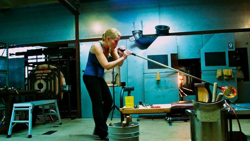 In this undated photo provided by April Wagner, Wagner works with a blow torch and hot glass in her Detroit, Mich., studio. (Sebastian Sullen/April Wagner via AP)