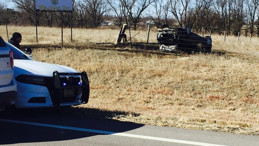 This photo provided by the Kansas Highway Patrol shows an overturned vehicle at the scene following a police chase that ended in a fiery crash Wednesday, March 1, 2017, near Wilson, Kan. The driver, Alex Bridges Deaton, was arrested after the crash. Authorities say Deaton is a suspect in the of shooting of a Kansas convenience store clerk and the kidnapping of two hikers in New Mexico while on the run after his girlfriend was killed and a jogger was shot in Mississippi. (Kansas Highway Patrol via AP)